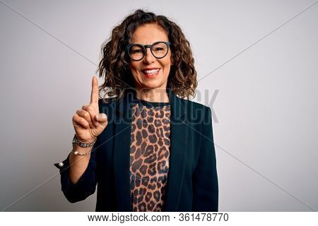 Middle age brunette business woman wearing glasses standing over isolated white background showing and pointing up with finger number one while smiling confident and happy.