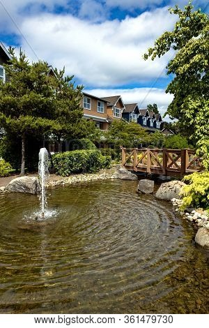 Residential District In Richmond City, A Village Of Townhouses With Pond And Fountain, Green Grass B