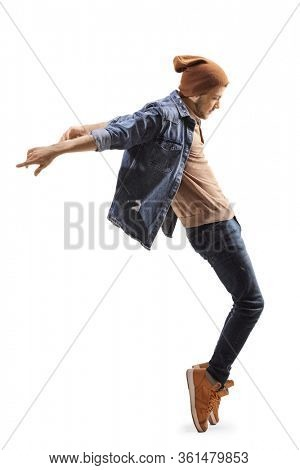 Full length profile shot of a young guy dancing on tiptoes isolated on white background