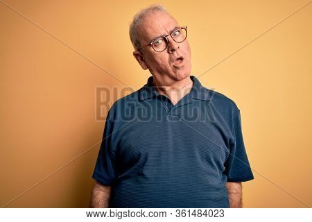 Middle age handsome hoary man wearing casual polo and glasses over yellow background In shock face, looking skeptical and sarcastic, surprised with open mouth