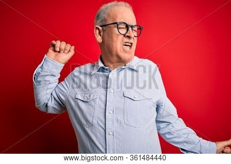 Middle age handsome hoary man wearing casual striped shirt and glasses over red background Dancing happy and cheerful, smiling moving casual and confident listening to music