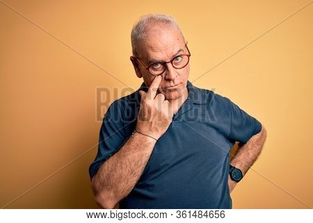 Middle age handsome hoary man wearing casual polo and glasses over yellow background Pointing to the eye watching you gesture, suspicious expression