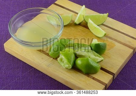 Lime Juice In Glass Bowl And Lime Wedges And Squeezed Limes On Wooden Cutting Board