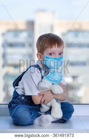 Little Masked Boy Plays With A Plush Dog On The Windowsill