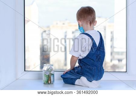 Little Boy In A Mask On Window Sill With Moneybox