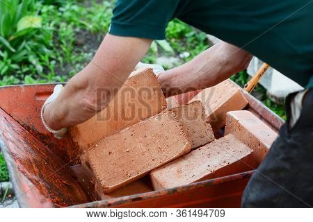 Bricklayer Is Taking Red Bricks From A Metal Wheelbaroow To Construct Masonry On A Construction Site