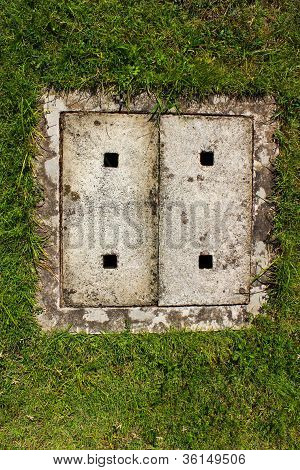 Cement Cover Of Drain On Filed.