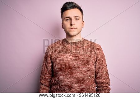 Young handsome caucasian man wearing casual winter sweater over pink isolated background Relaxed with serious expression on face. Simple and natural looking at the camera.