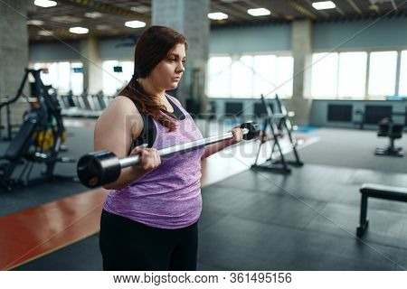Overweight woman with dumbbells on brench in gym