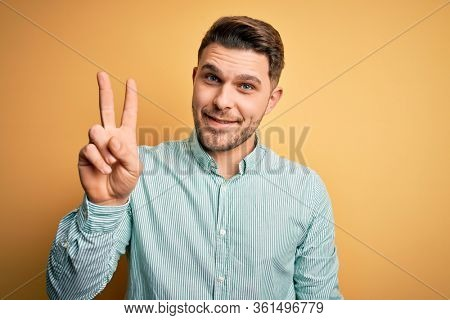 Young business man with blue eyes wearing elegant green shirt over yellow background showing and pointing up with fingers number two while smiling confident and happy.