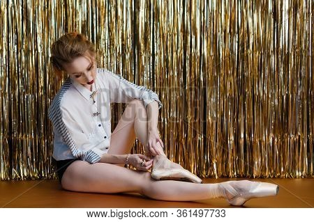 Young Attractive Ballerina Is Tying Ribbons On Pointe Shoes Backstage. Girl Is Preparing For Perform
