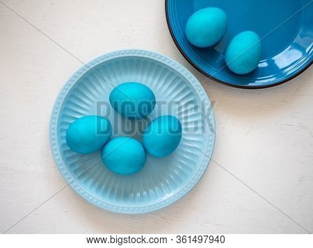 Two Plates In Blue Tones With Easter Blue Eggs On A White Wooden Table