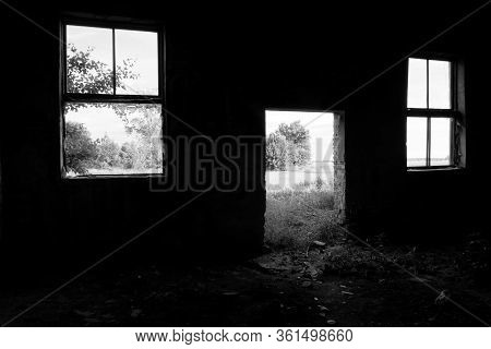Two Broken Windows And An Empty Doorway In The Wall Of An Abandoned Building.