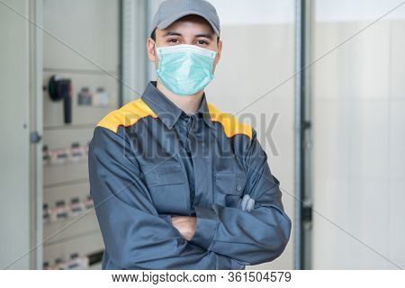 Portrait of an electrician in front of an industrial electric panel in a factory while wearing a mask, coronavirus pandemic concept