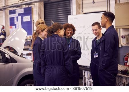 Students Studying For Auto Mechanic Apprenticeship At College Standing By Whiteboard