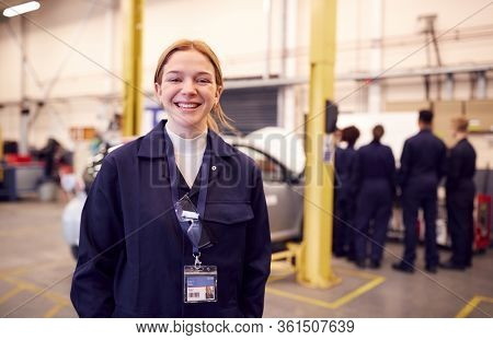 Portrait Of Female Student With Safety Glasses Studying For Auto Mechanic Apprenticeship At College
