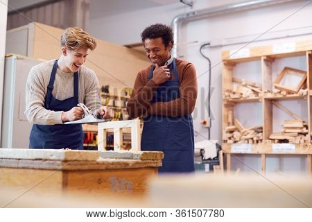Tutor With Male Carpentry Student In Workshop Studying For Apprenticeship At College