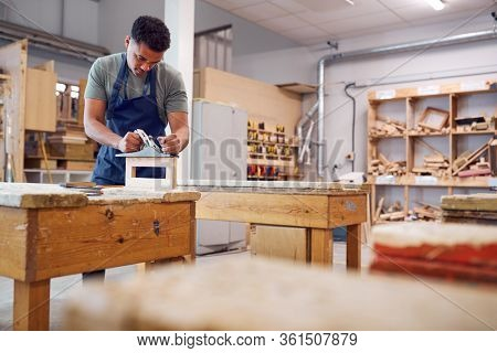 Male Student Studying For Carpentry Apprenticeship At College Using Wood Plane