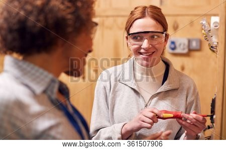 Female Tutor With Trainee Electrician In Workshop Studying For Apprenticeship At College