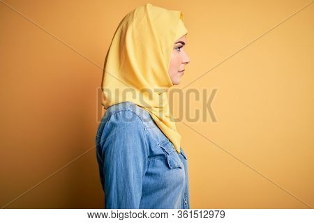Young beautiful girl wearing muslim hijab standing over isolated yellow background looking to side, relax profile pose with natural face with confident smile.