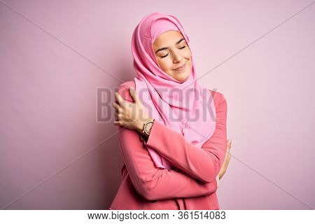 Young beautiful girl wearing muslim hijab standing over isolated pink background Hugging oneself happy and positive, smiling confident. Self love and self care