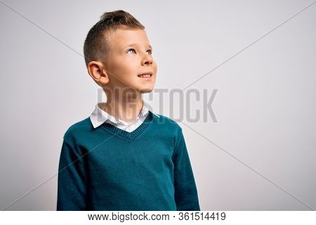 Young little caucasian kid with blue eyes standing wearing elegant clothes over isolated background looking away to side with smile on face, natural expression. Laughing confident.