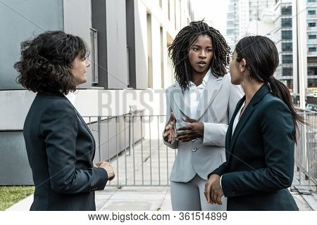 Serious Multiethnic Colleagues Talking Near Office Building. Business Women Meeting Outside In City.