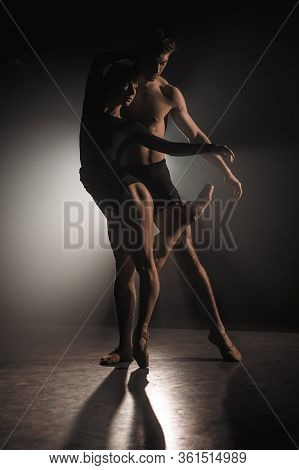 Beautiful Young Acrobats Or Gymnasts On Floodlights Background. Professional Ballet Couple Dancing I