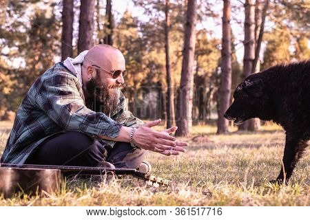 Man Hipster Playing With Dog In Nature. Man Embracing Dog In Nature. Close Up Of Man With Stray Dog.
