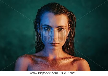 Portrait Of Young Beautiful Model Girl With Original Golden Make-up And Sparkles On Blue Background.