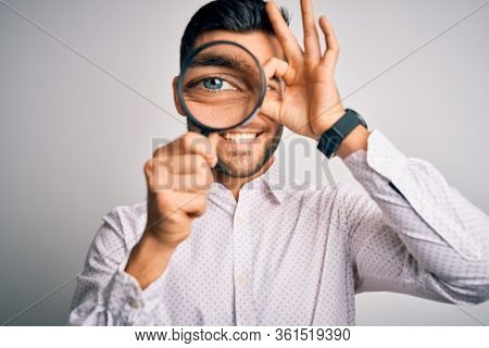 Young detective man looking through magnifying glass over isolated background with happy face smiling doing ok sign with hand on eye looking through fingers