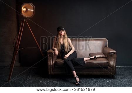 Blonde Model Posing Sitting On The Couch In Dark Studio. Young Attractive Fashion Model Posing On Da