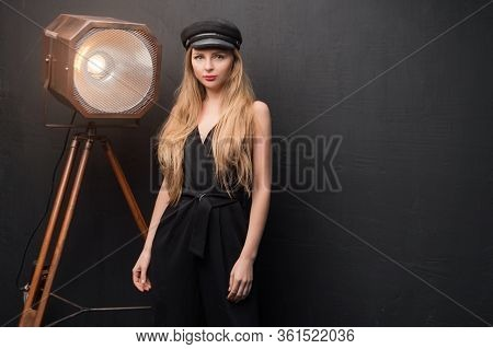 Blonde Model Posing In Dark Studio. Young Attractive Fashion Model Posing On Dark Background. Space