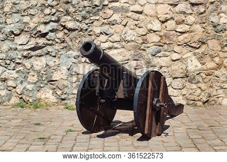 Old Cannon Over Stone Wall. Old Castle. Ancient Cannon On Wheels. Museum Piece Outdoor.