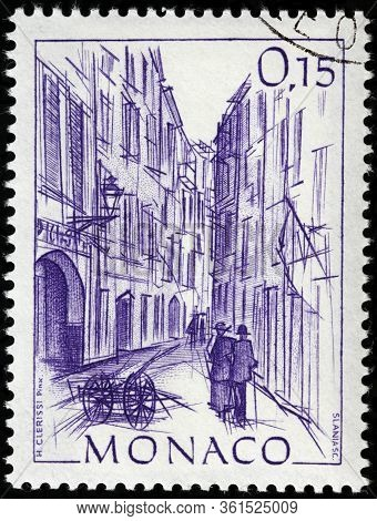 Luga, Russia - April 10, 2020: A Stamp Printed By Monaco Shows View Of Rue Basse In Monte Carlo, Cir