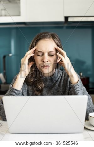 Closeup Portrait Of Young Beautiful Woman Thinking Hard And Working On Laptop Computer In Kitchen. C