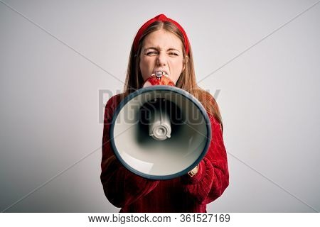 Young caucasian woman shouting on protest through megaphone. Yelling excited on ludspeaker talking and screaming news