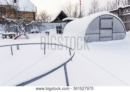 Winter, Snow, Frost In The Garden. Childish Snow-covered Slide In The Garden. Trampoline On White Sn