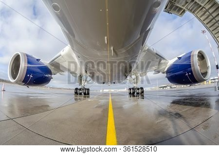Passenger Wide-body Plane Is Parked On The Airport Apron. Aircraft Fuselage, Engine And Main Landing
