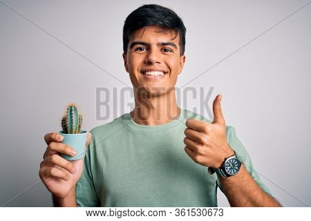 Young handsome man holding small cactus plant pot over isolated white background happy with big smile doing ok sign, thumb up with fingers, excellent sign