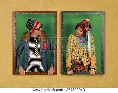 A Couple Of Freaks Hold Picture Frames And Look At Each Other On A Yellow Background. Crazy People P