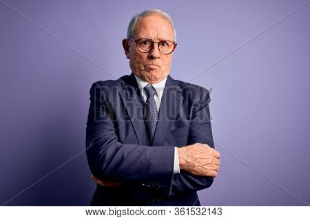 Grey haired senior business man wearing glasses and elegant suit and tie over purple background skeptic and nervous, disapproving expression on face with crossed arms. Negative person.