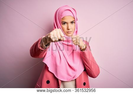 Young beautiful girl wearing muslim hijab standing over isolated pink background Punching fist to fight, aggressive and angry attack, threat and violence