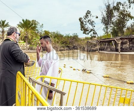 QASR El-YAHUD, ISRAEL - MARCH 2, 2020: Baptism ceremony. The site of the baptism of Jesus Christ. Jordan river. The priest blesses a man in a white baptismal shirt.