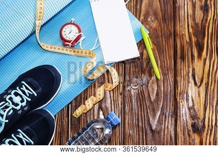 Healthy Lifestyle And Sports Background. Sports Shoes, Notepad And Pen, And Water Bottle On Wooden B