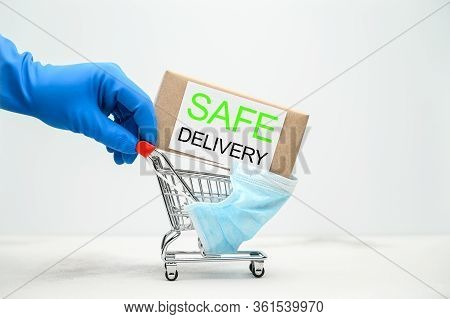 Safe Home Delivery. A Hand In A Blue Medical Glove Holds A Shopping Cart With A Parcel On A Light Ta