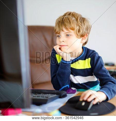 Little School Kid Boy Making School Homework On Computer. Child Learning On Pc. Hard-working Boy Mak