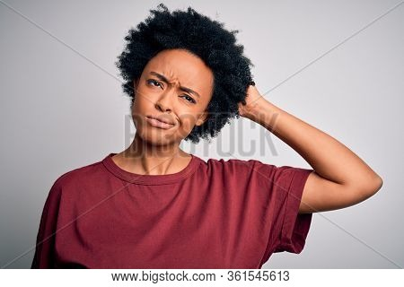 Young beautiful African American afro woman with curly hair wearing casual t-shirt standing confuse and wonder about question. Uncertain with doubt, thinking with hand on head. Pensive concept.