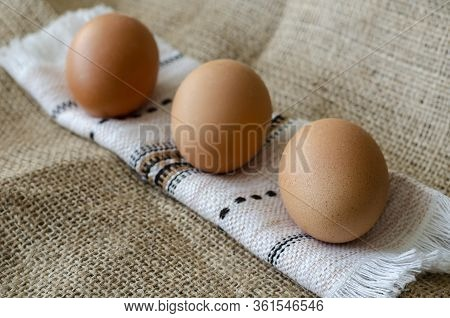 Three Brown Chicken Eggs On Burlap. A Line Of Raw Farm Eggs On A Rushnyk. A Rolled Towel With Eggs O