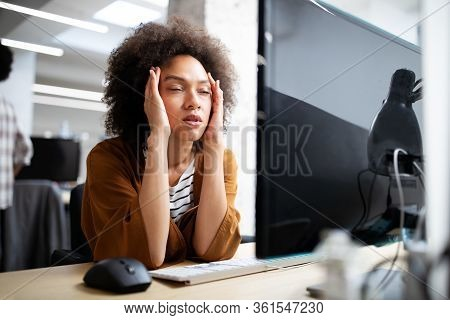 Overworked And Frustrated Young Woman In Front Of Computer In Office